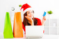 smiling young woman holding credit card with tablet . Christmas shopping concept. - PhotoDune Item for Sale