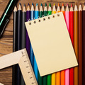 Many Different Colored Pencils On Wooden Table And Empty Notebook Blank. - PhotoDune Item for Sale