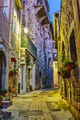 Narrow street with flowers in the old town Peille in France. Nig - PhotoDune Item for Sale