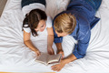 Couple Lying on Bed Reading A Book - PhotoDune Item for Sale