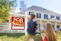 Curious Family Facing Sold For Sale Real Estate Sign and Beautiful New House. - PhotoDune Item for Sale