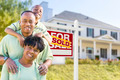 Happy African American Family In Front of Sold For Sale Real Estate Sign and House. - PhotoDune Item for Sale