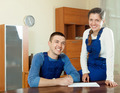 Happy smiling young  workers in uniform with financial documents - PhotoDune Item for Sale