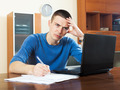 Sad guy  with laptop and financial documents at home interior - PhotoDune Item for Sale