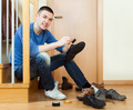 Happy man sitting on stairs and cleaning footwear - PhotoDune Item for Sale