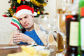 Sick hungover man in Santa hat with glass of water - PhotoDune Item for Sale