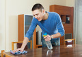 man dusting wooden table with rag and cleanser at home - PhotoDune Item for Sale