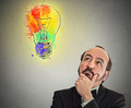 Man with thoughtful expression and light bulb over his head