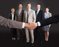 Businessmen Shaking Hands With Confident Team Standing Behind - PhotoDune Item for Sale