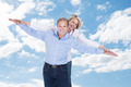 Couple With Arms Outstretched Standing Against Cloudy Sky - PhotoDune Item for Sale
