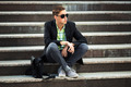 Young man with a mobile phone sitting on the steps - PhotoDune Item for Sale