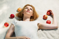 Happy young woman with apples lying on the cover - PhotoDune Item for Sale