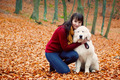Young pretty woman hugging cute white puppy dog in autumn fall park. - PhotoDune Item for Sale