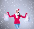 Composite image of festive brunette holding shopping bags against grey vignette