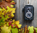 Retro camera on wooden table with autumn leaves - PhotoDune Item for Sale