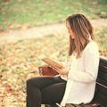 Woman reading a book at bench in autumn park - PhotoDune Item for Sale