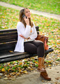 Happy young woman talking on phone in Autumn park - PhotoDune Item for Sale
