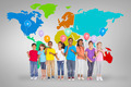 Elementary pupils holding balloons against grey vignette with world map