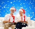 happy senior couple in santa hats with gift boxes - PhotoDune Item for Sale