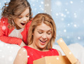 smiling mother and daughter with gift box at home - PhotoDune Item for Sale