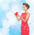 smiling young woman in red dress with gift box - PhotoDune Item for Sale