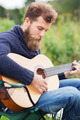 man with beard playing guitar in camping - PhotoDune Item for Sale