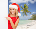 smiling young woman in santa hat with white board - PhotoDune Item for Sale
