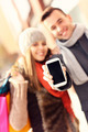 Couple showing smartphone while shopping - PhotoDune Item for Sale
