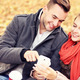 Young couple on a bench with smartphone in the park - PhotoDune Item for Sale