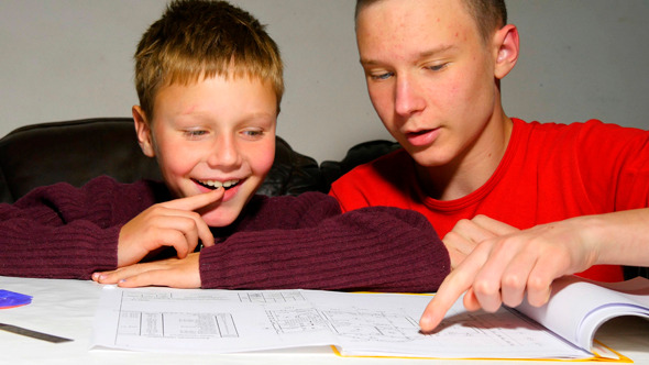 Teen Explaining Architectural Plan To His Brother