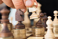 Hand Playing Chess Stacked On Coins - PhotoDune Item for Sale