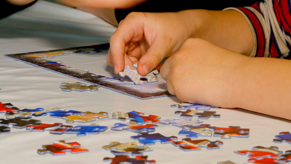 Child Hands Assemble Jigsaw Puzzle
