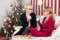 Two women chatting next to the Christmas tree - PhotoDune Item for Sale