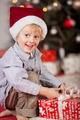 Happy smiling little boy unwrapping a Xmas gift - PhotoDune Item for Sale