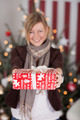 Young woman holding out a Christmas gift - PhotoDune Item for Sale