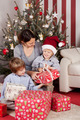 Young family opening Christmas gifts - PhotoDune Item for Sale