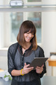 Smiling woman reading a handheld tablet - PhotoDune Item for Sale
