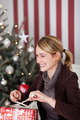 Smiling woman unwrapping her Christmas gift - PhotoDune Item for Sale