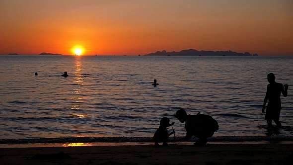 Mother with Child near Sea at Sunset