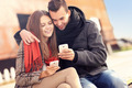 Young couple sitting on a bench and using smartphones - PhotoDune Item for Sale