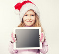 Child in christmas hat with tablet - PhotoDune Item for Sale
