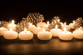 Burning candles with pine apples at a black background - PhotoDune Item for Sale