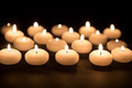 Several white candles with selective focus at a black background - PhotoDune Item for Sale