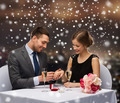 smiling couple with red gift box at restaurant - PhotoDune Item for Sale