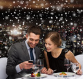 smiling couple with smartphone at restaurant - PhotoDune Item for Sale