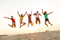 smiling friends dancing and jumping on beach - PhotoDune Item for Sale