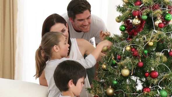Brother and Sister Decorating a Christmas Tree with Their Parents