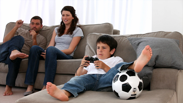 Cute Little Boy Playing Video Games and Parents Enjoying Watching