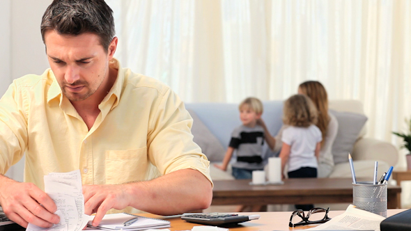 Casual Man Calculating His Bills With His Family In The Background