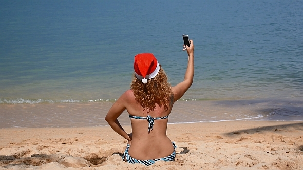 Santa Woman on the Beach Taking Selfie